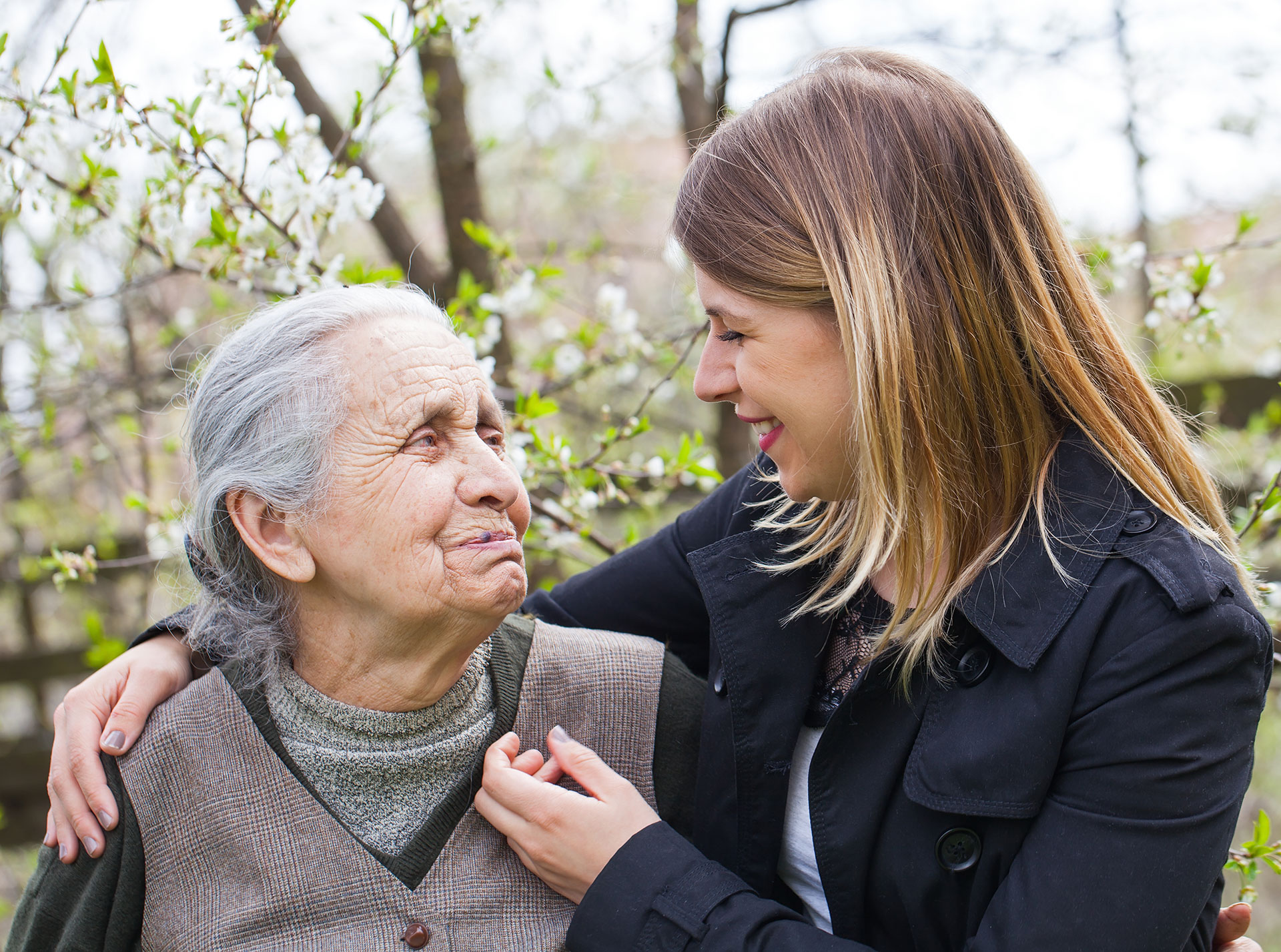 woman with arm around elderly woman outside